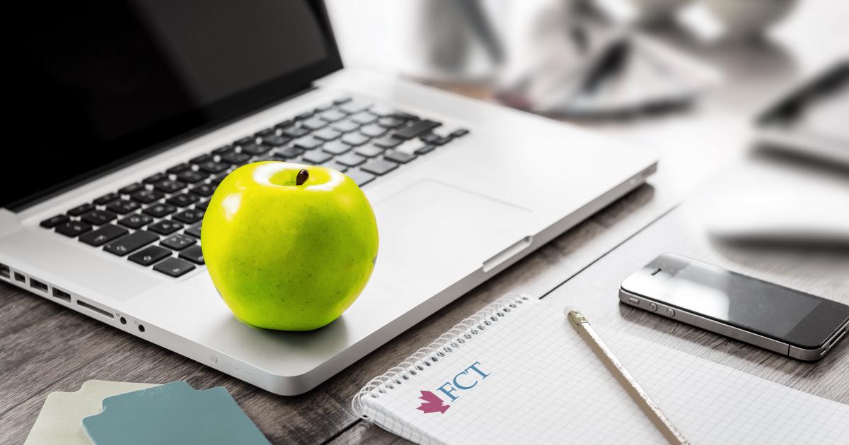 A green apple on a laptop