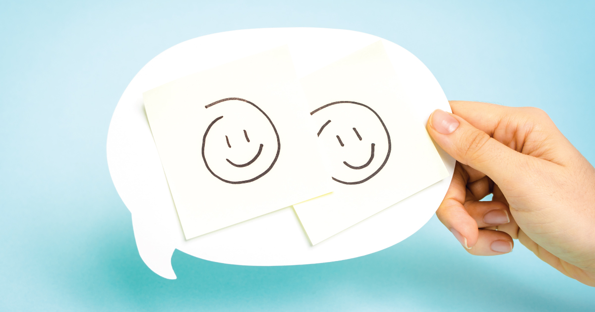 Two happy face drawings in a conversation bubble