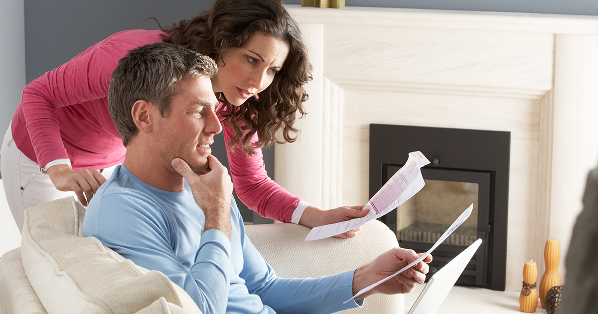 A couple reviewing financial documents in their living room