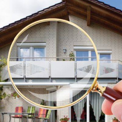 Magnifine glass inspecting a house