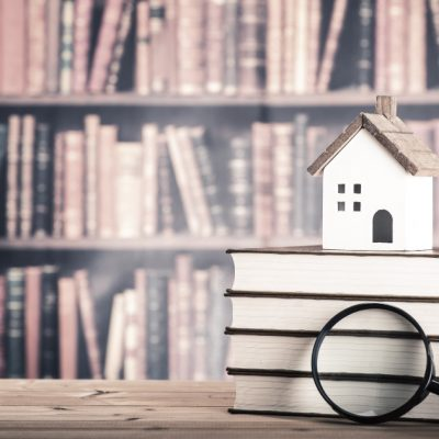 Library of books with a house and a magnifine glass for first-time home buyer