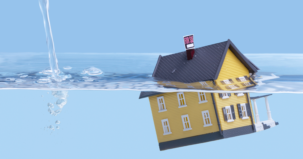 A house with a for sale sign floating in a glass of water