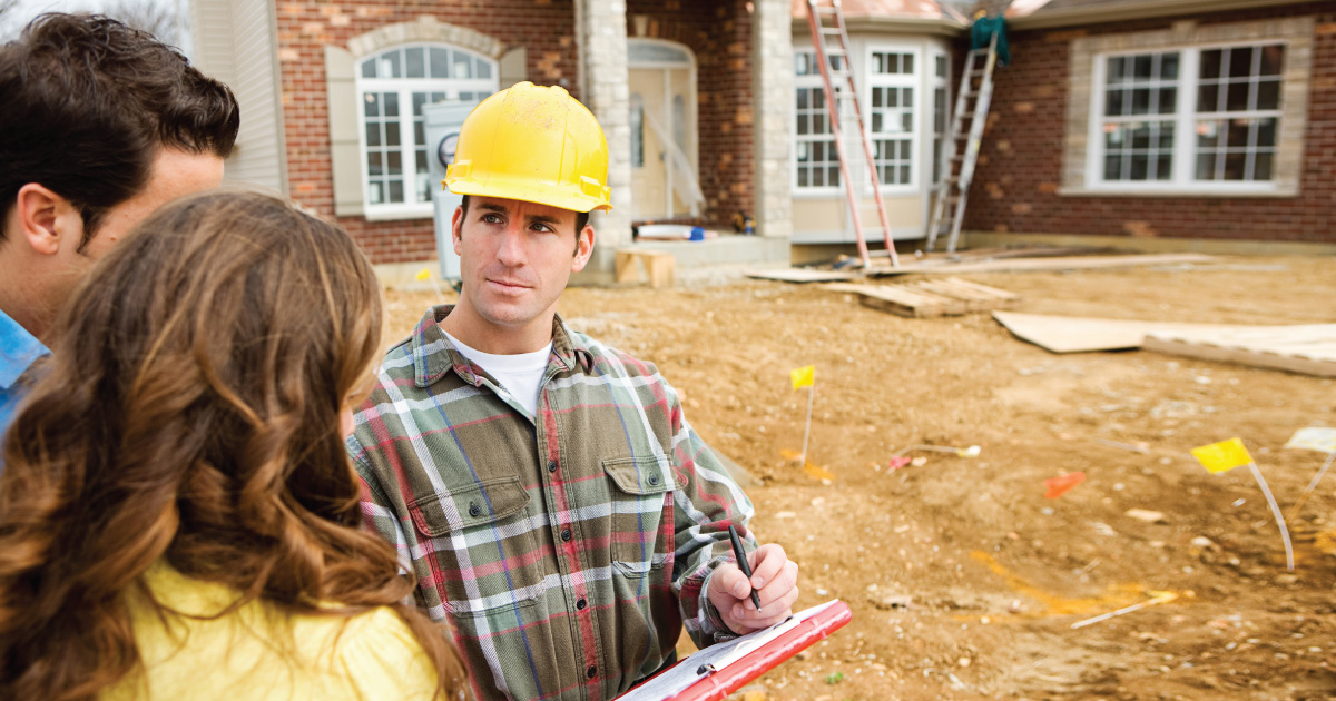 Building Inspector talking to a couple outside of their home