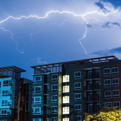Condo building with lightning in the sky