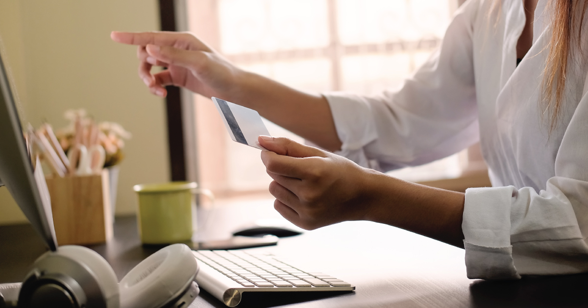 A woman holding a credit card while shopping online on her desktop computer