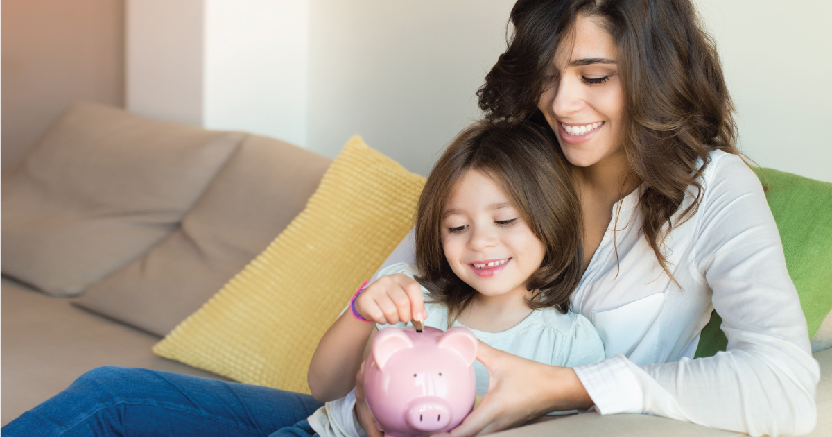 mother and daughter placing a coin into a piggy bank