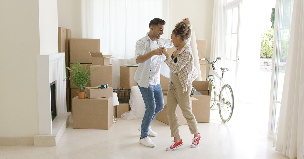 Couple Dancing as they unpack boxes in their new home