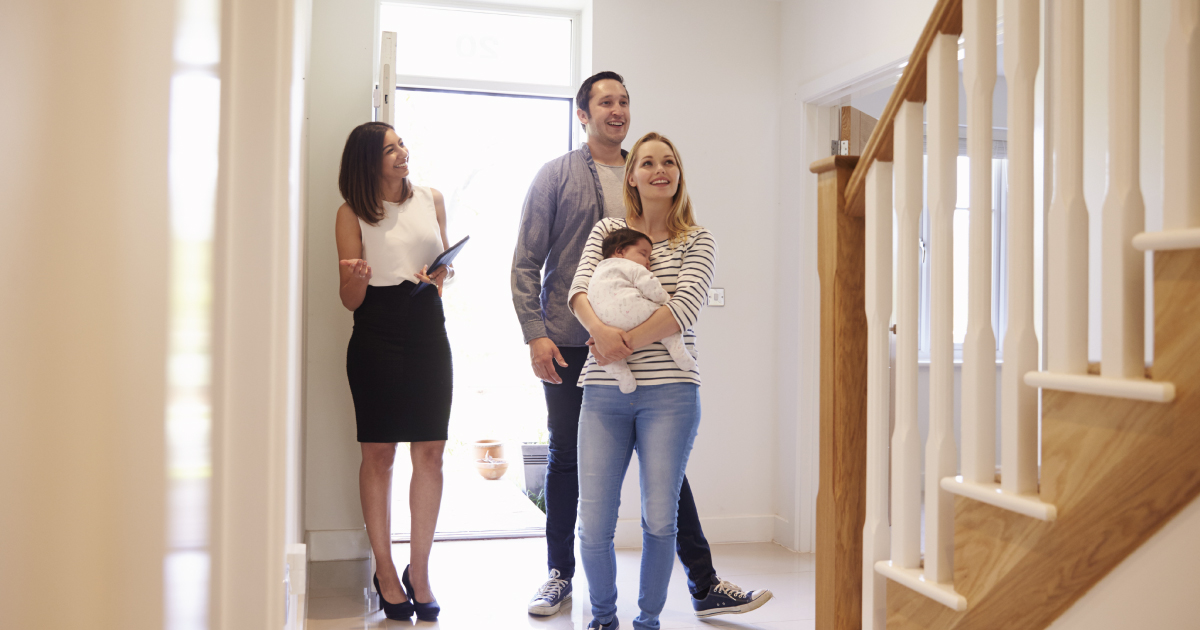 First time homebuyers with their baby and a real estate agent entering their new home