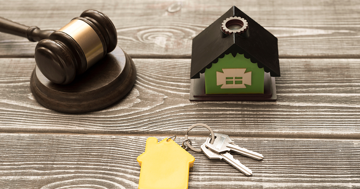 Toy Home, keys, and gavel on a desk