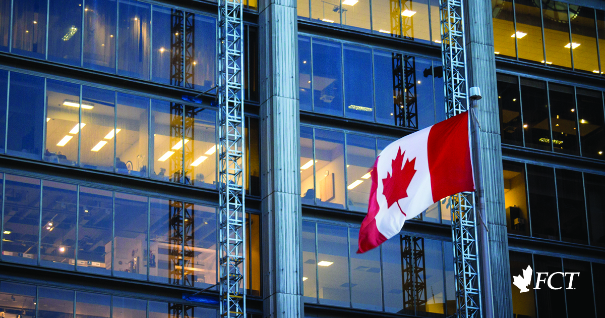 A large Canadian Flag next to an office tower