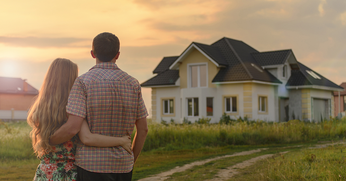 Couple standing with arms around each other dreaming of owning home and getting a mortgage