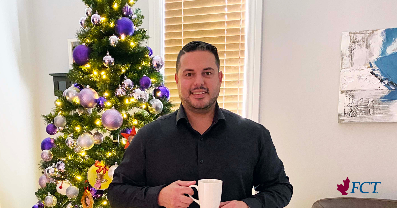 man holding a cup with a Christmas tree behind him