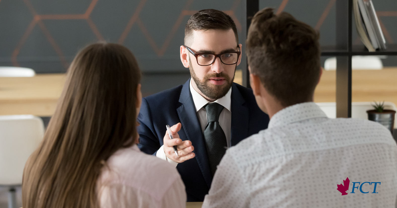 lender explains serious topic to couple in his office