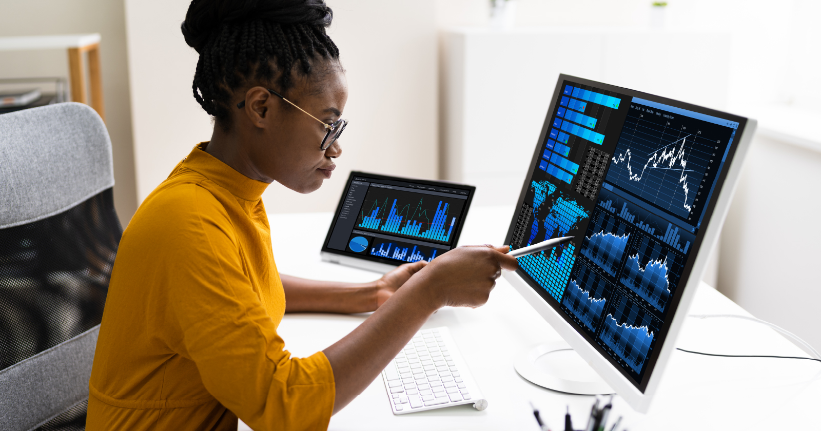 Photo of a professional sitting at her desk with two market terminals showing her data