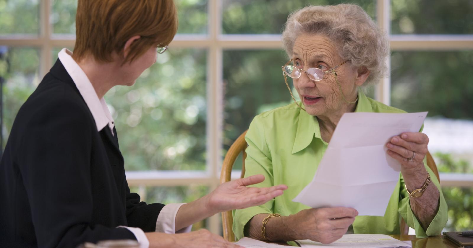 femme âgée surprise par des informations sur papier, une avocate lui parle