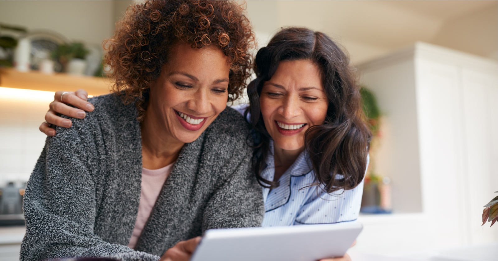 photo of two women huddled together at their kitchen counter and smiling as they read a tablet together