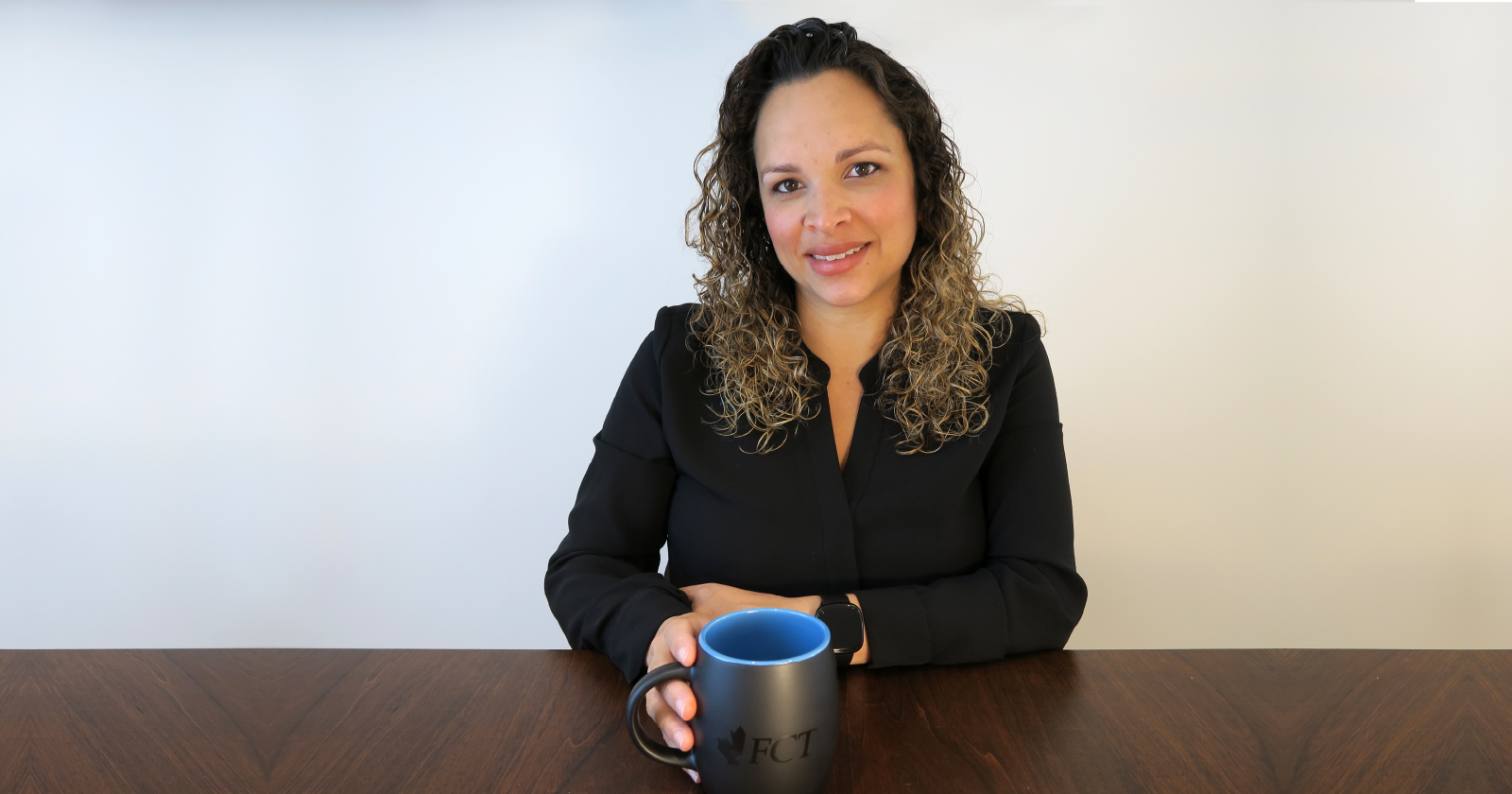 photo of Brenna Charles seated behind a table, smiling as she holds a coffee cup with FCT on it