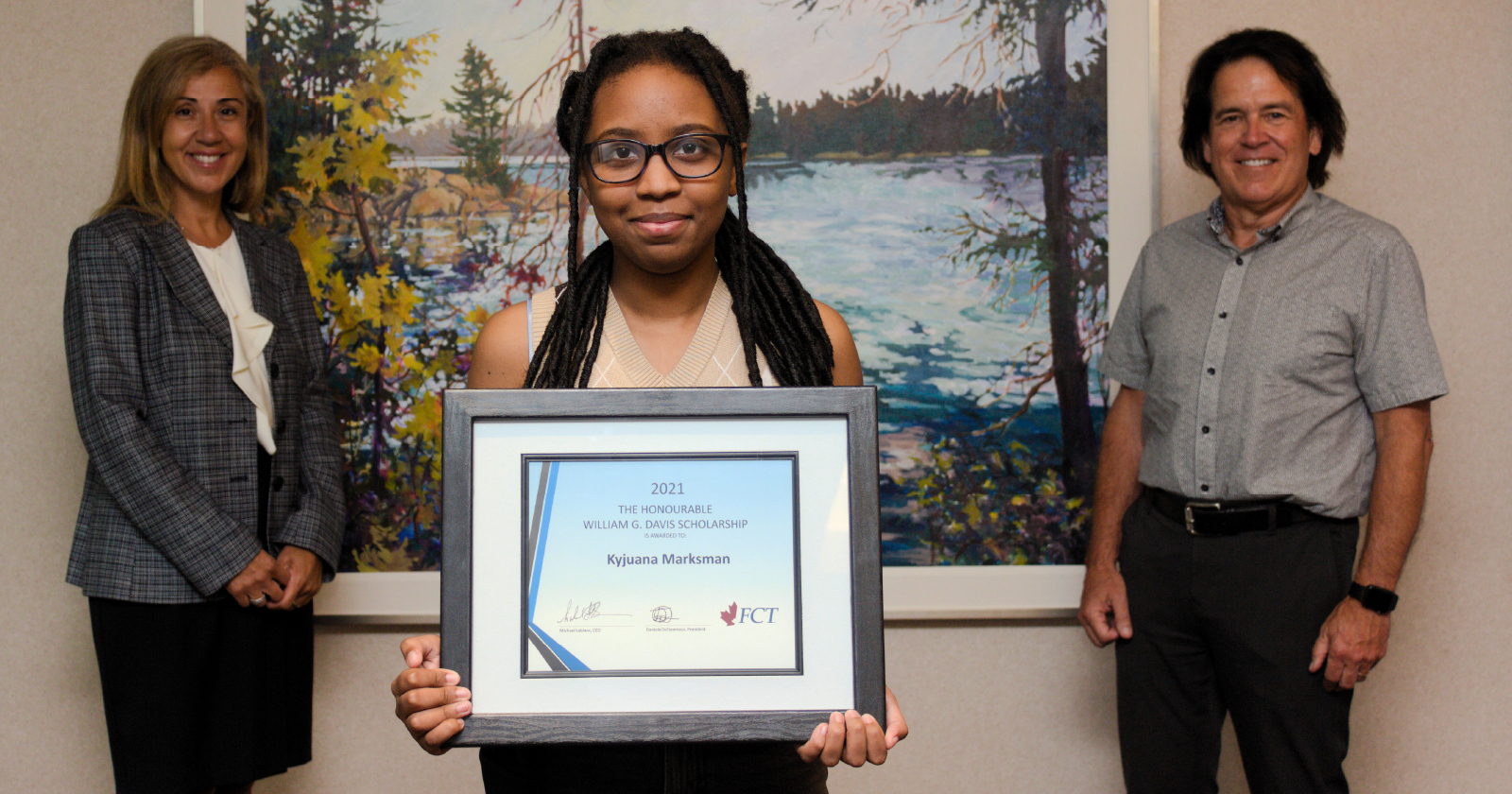 photo of Jyjuana Marksman holding her scholarship award with Daniela DeTommaso standing behind and to the left, Michael LeBlanc standing behind to the right.